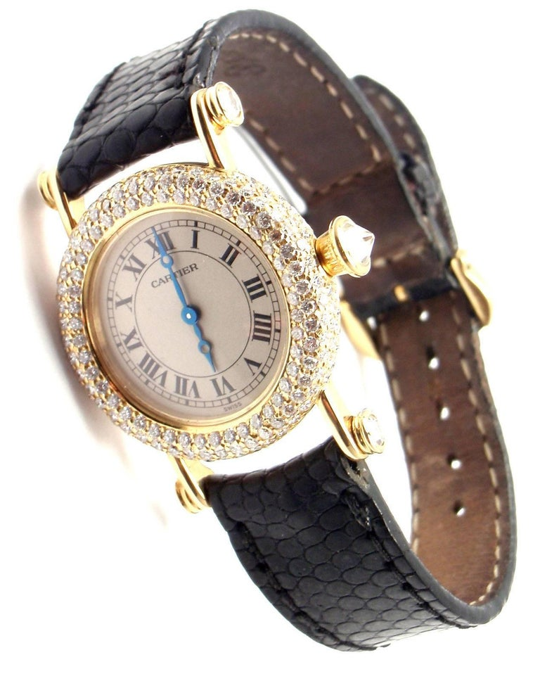 18k Yellow Gold Diamond Diabolo Ladies Wristwatch by Cartier.   Brand: Cartier Style Number: Diabolo Series: Medium Size Case Material: 18k Yellow Gold with Diamonds Dial Color: Off white with Roman Numerals Movement: Quartz Functions: Hours,