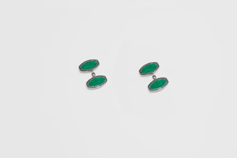 A pair of sterling silver and vitreous enamel Art Deco cufflinks. This very handsome tonneau shaped cufflink is beautifully hand painted with a border of elongated Greek key design picked out in black enamel, and the center of each panel is hand