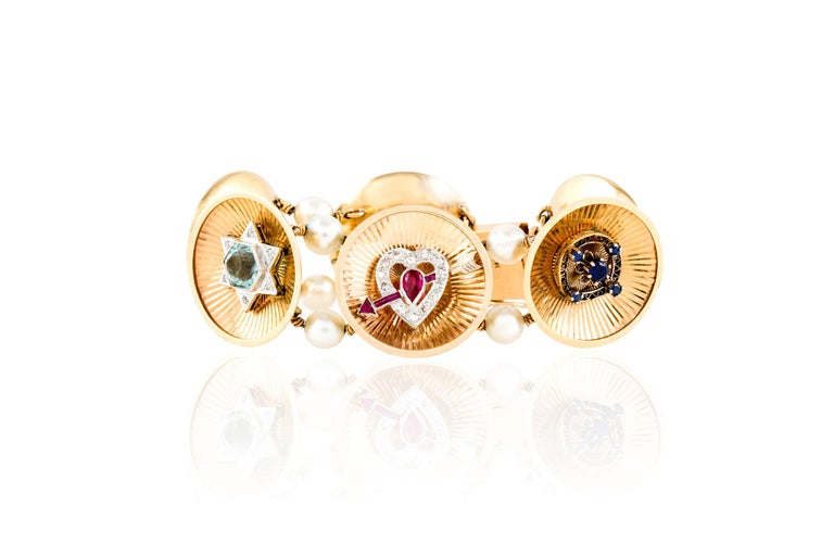 Vintage bracelet, finely crafted in 14 k yellow gold with six art deco, charms finely crafted in platinum with diamonds, sapphires and rubies. Each slide is devided with beautiful pearls. Length 7.25 inches Circa 1940's.