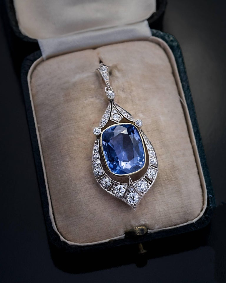 Made in Moscow around 1930 A vintage silver-topped 14K gold Art Deco pendant features an impressive 12.47 ct natural unheated sapphire from Ceylon. The sapphire is set in an elaborate frame embellished with transitional and old cut diamonds