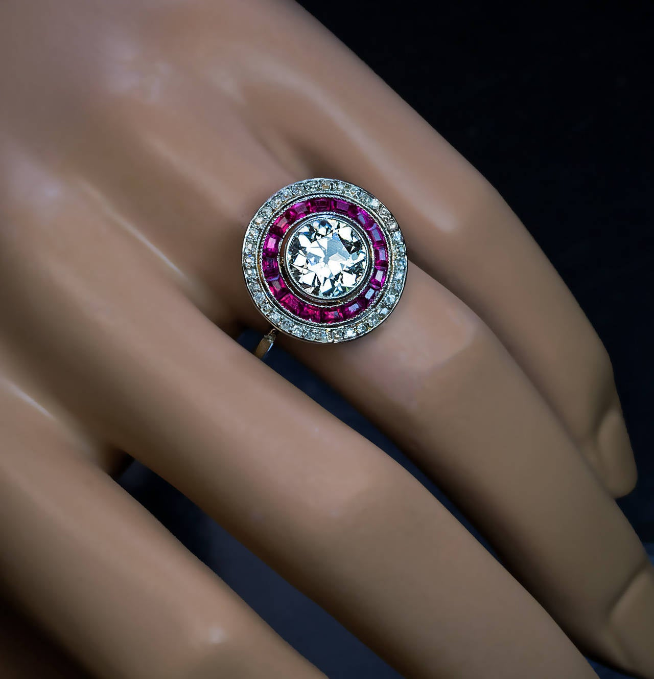 Edwardian / Early Art Deco, circa 1915  The ring is centered with a bright white and sparkling old European cut diamond (approximately 2.10 ct) encircled by a row of French cut rubies and further set with a border of old cut diamonds