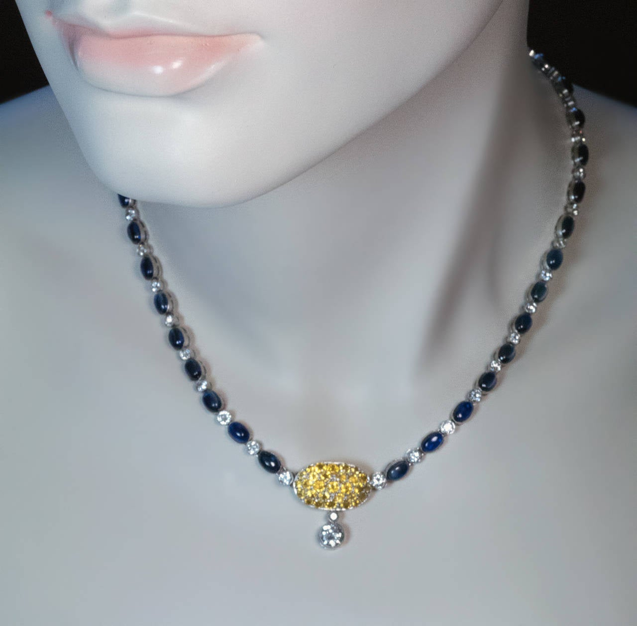 The necklace is bezel-set with 39 cabochon cut blue sapphires and 40 old European and transitional cut diamonds. The oval clasp with a two-stone diamond pendant is densely set with round faceted yellow sapphires. 