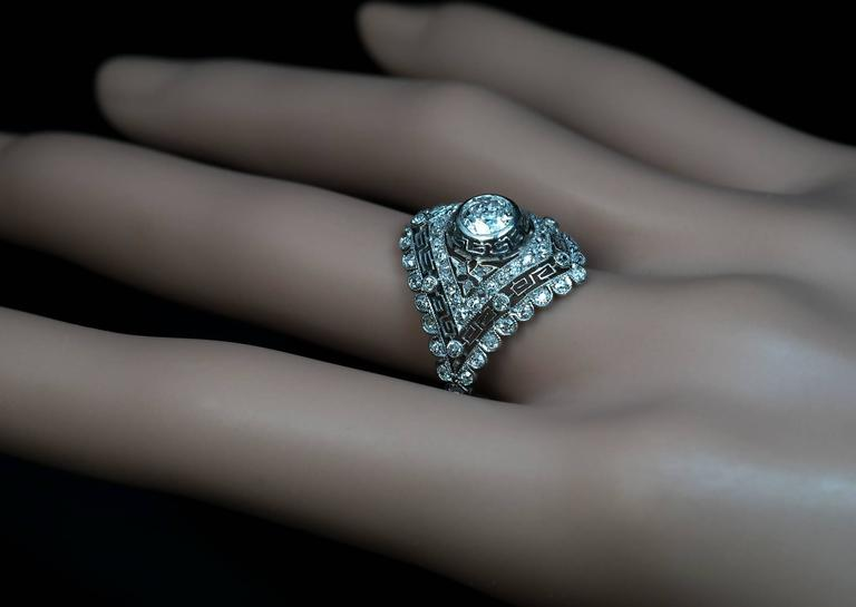 Portuguese, circa 1938  an openwork platinum ring with a Greek key motif centered with a bezel-set old European cut diamond (approximately 0.50 ct) surrounded by numerous old single cut diamonds