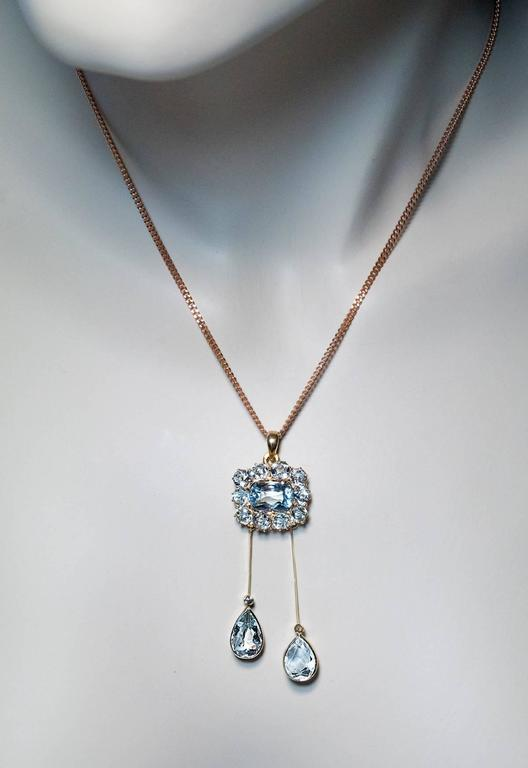 Made in St. Petersburg between 1908 and 1917  A 14K gold pendant is set with sparkling cool blue various-cut aquamarines.  Marked with 56 zolotnik old Russian gold standard and maker's initials.  Length 58 mm (2 1/4 in.)  Sold without chain
