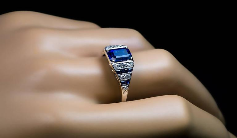 Circa 1920  A platinum hand-crafted ring is centered with an emerald cut natural sapphire (8.2 x 5.85 x 4.4 mm, approximately 2.11 ct) of a beautiful cornflower blue color.  The shoulders of the ring are vertically channel set with old single
