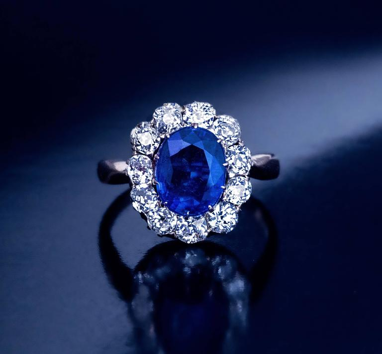 Circa 1910  A 14K gold ring is centered with a cornflower blue kyanite (measuring 9.5 x 7.5 x 4.5 mm, approximately 2.47 ct.) surrounded by 11 sparkling bright white old mine cut diamonds (H-I color, mostly VS clarity).  Estimated total diamond