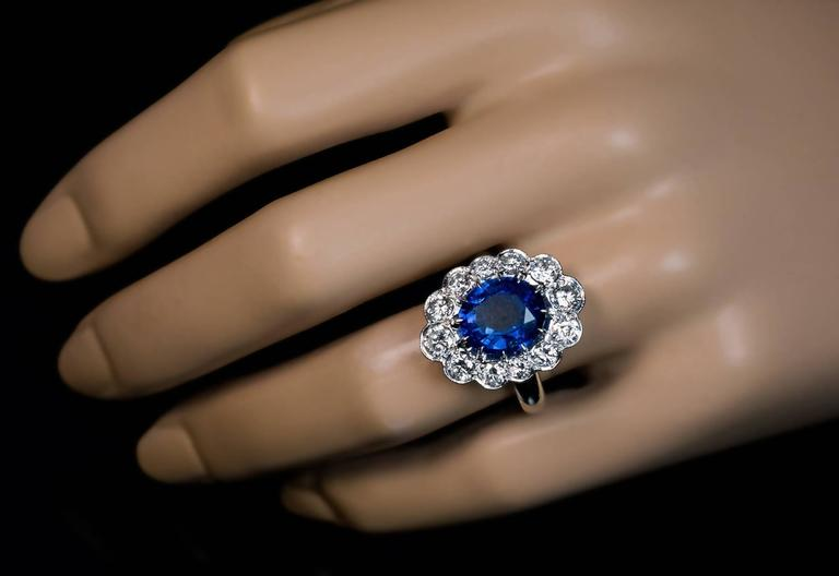An impressive French cluster ring from the 1940s -1950s.  The handcrafted platinum ring features a natural oval blue sapphire (measuring 10.75 x 9.4 x 4.8 mm, approximately 3.88 ct), framed by twelve bright white brilliant diamonds. Estimated