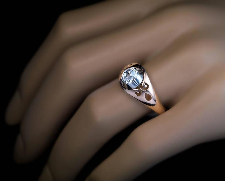 Russian, made between 1908 and 1917  A 14K rose gold ring is centered with a sparkling antique cushion cut diamond (6.7 x 5.4 x 4.2 mm, approximately 1.17 ct, H color, VS1 clarity) set in a silver bezel and flanked by openwork shoulders.  The