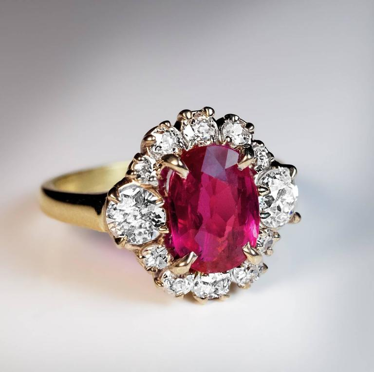 A silver topped 18K gold ring is centered with an oval natural unheated pink-red 2.71 ct ruby from Burma (Myanmar). The ruby is framed by bright white (F-G color) old mine cut diamonds (estimated total weight 1.25 ct).
