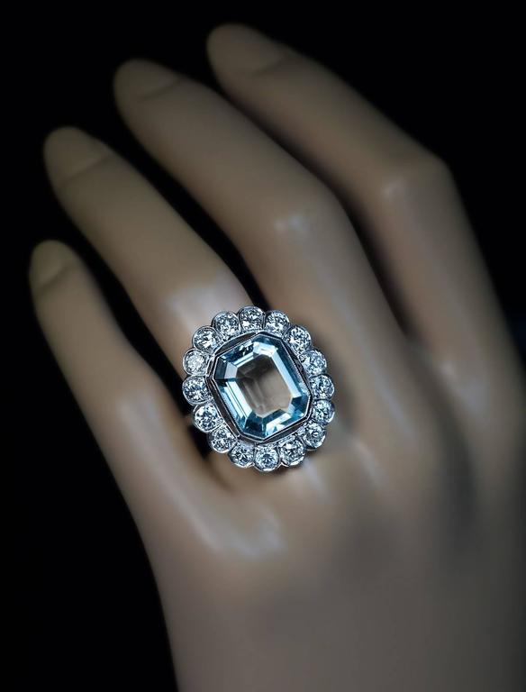 An impressive hand-crafted platinum ring from Art Deco era is centered with an emerald cut cool greenish-blue aquamarine (measuring 14.3 x 12 x 6.45 mm, approximately 7.58 ct) framed by sixteen old European and transitional cut brilliant