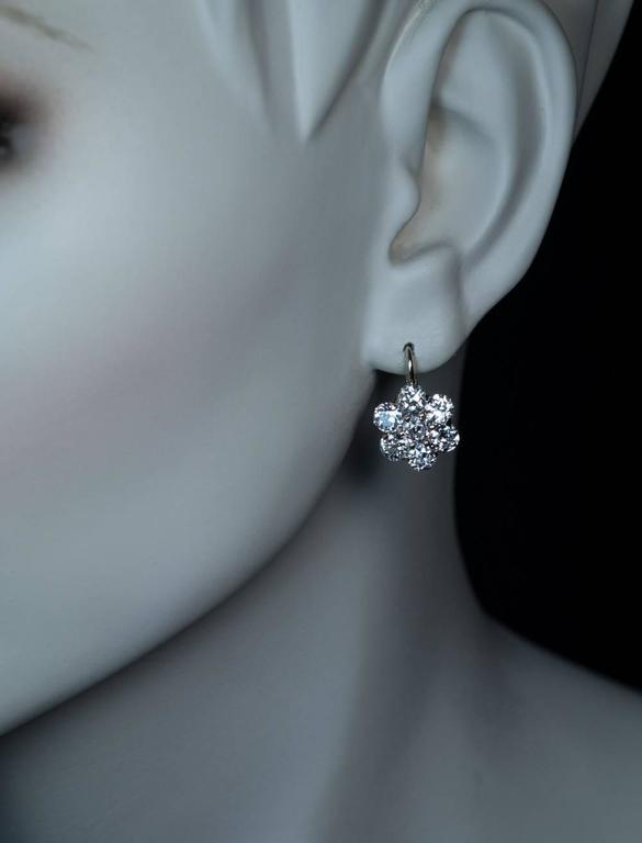 Made in Moscow between 1908 and 1917 A superb pair of antique Russian cluster earrings finely crafted in silver topped 14K gold. The earrings are set with 14 sparkling bright white old European cut diamonds. The diamonds are of a top quality for