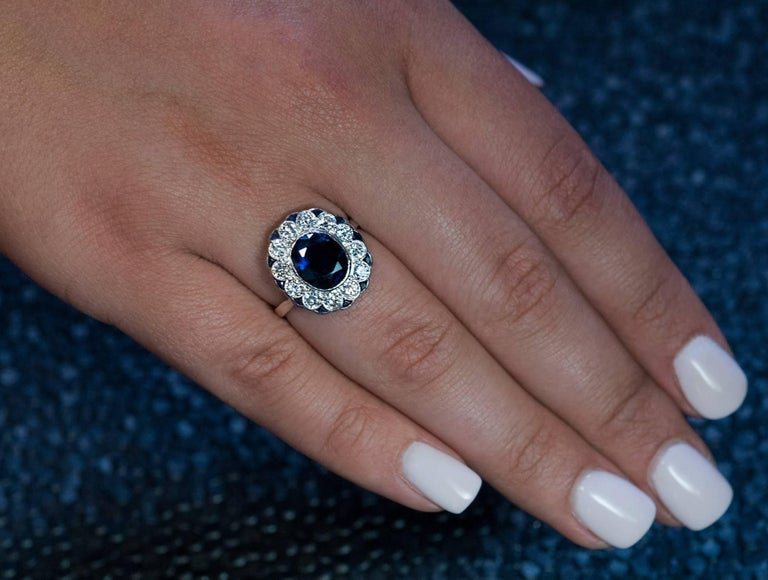 Circa 1950s A vintage mid-century 14K white gold ring is centered with a bezel set natural sapphire (9.2 x 7.8 x 4.6 mm, approximately 2.64 ct) surrounded by 12 bright white brilliant cut diamonds (F-G color, VS2-SI2 clarity), in turn, outlined by