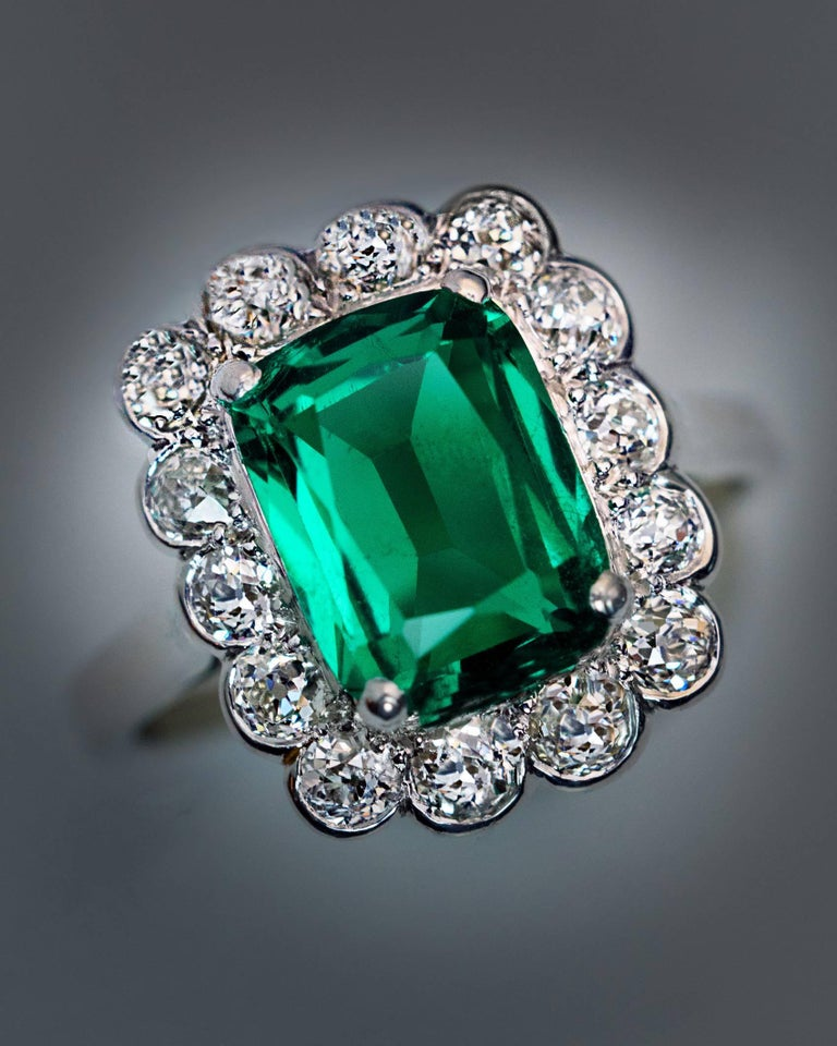 Circa 1925  This vintage French platinum (head) and 18K white gold (shank) engagement ring features a very rare untreated 2.31 ct Colombian emerald. The cushion cut emerald is extremely clean and full of life. The center stone is framed by chunky