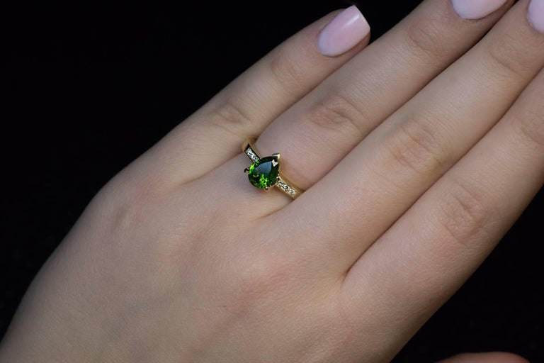 "A contemporary 18K gold ring is centered with a grass green 1.45 ct pear cut Russian demantoid garnet flanked by bright white (F color) diamonds.  The demantoid has some fine ""horsetails"", a unique feature of demantoids mined in the Ural"