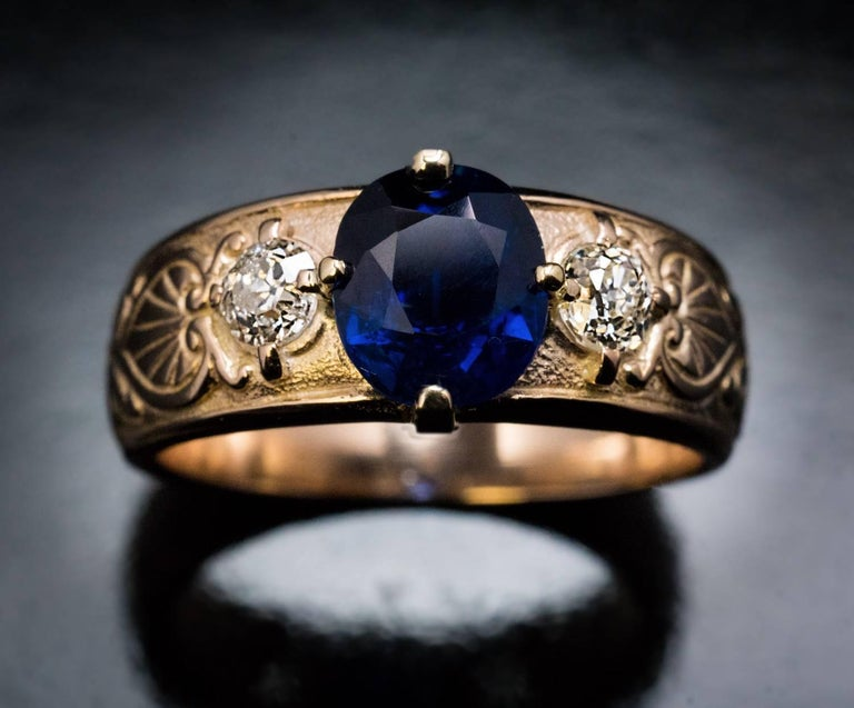 Circa 1910  An antique Russian 14K gold ring features a 1.97 ct natural sapphire of a deep royal blue color. The sapphire is flanked by two chunky old mine cut diamonds (approximately 0.24 ct and 0.22 ct). The sides of the ring are carved with