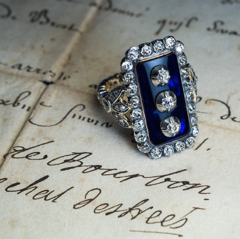 This impressive late 18th century, circa 1790, silver-topped gold ring is vertically set with a large cobalt blue glass plaque centered with three old cut diamonds set in silver cut down settings. The glass plaque is framed by 24 chunky old mine cut