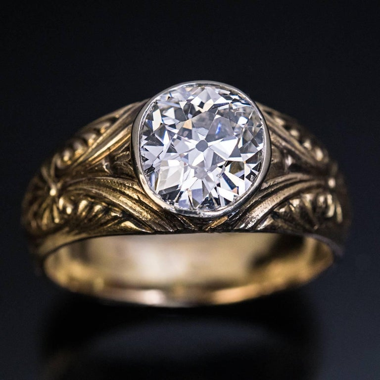 Made in Moscow between 1908 and 1917  An antique Russian 14K gold ring is centered with a sparkling 1.85 ct old mine cut diamond (I color, SI1 clarity). The diamond is set in a silver bezel. The sides of the ring are carved with Art Nouveau