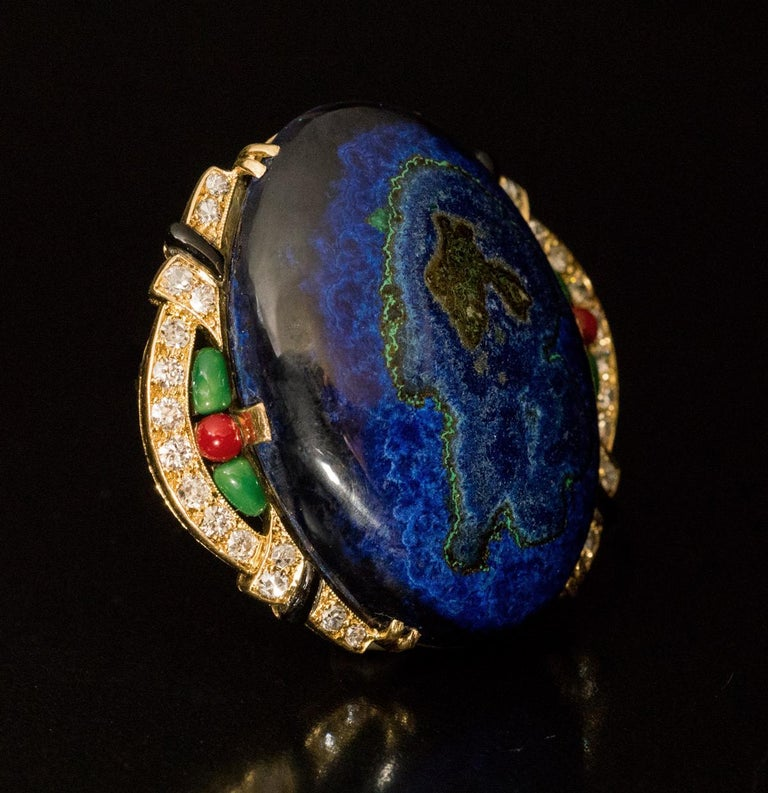 Circa 1925  This remarkable vintage French Art Deco brooch / pin features an oval cabochon cut azurite malachite set in an elaborate, slightly asymmetrical 18K gold bezel.  The bezel is embellished with bright white old cut diamonds (F-G color, SI