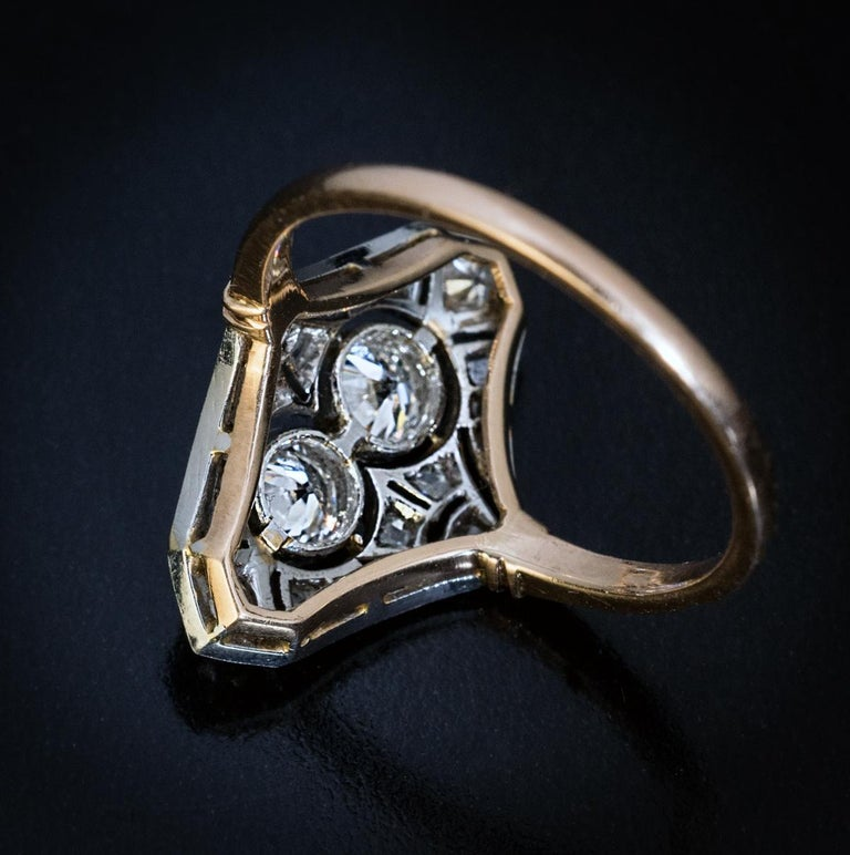 Circa 1910  An Edwardian era openwork milgrain engagement ring is finely crafted in platinum over 14K gold. The ring is centered with two sparkling old European cut diamonds  (approximately 0.25 ct and 0.27 ct) framed by old mine and rose cut