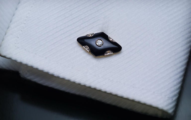 1920s  A pair of stylish Art Deco double sided cufflinks is crafted in 18K gold and platinum. The cufflinks are set with rhombus-shaped carved black onyx panels with smooth edges accented by old mine and rose cut diamonds. The diamonds are set in