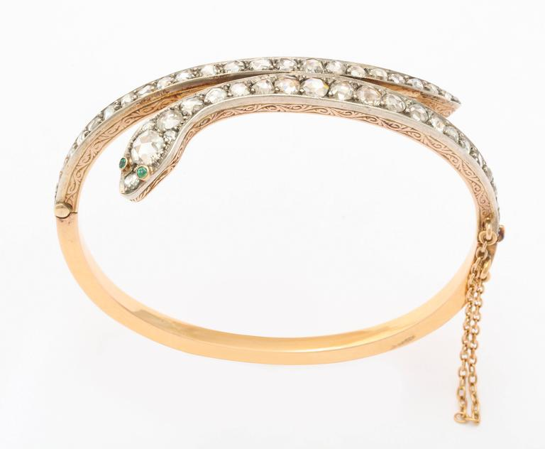 It is easy being Green when green eyes gaze at you from a diamond serpent bracelet of 15kt gold made in Victorian England c. 1860. The serpent cunningly wraps the wrist with the head and tail sections a glitter with antique diamonds. All stones are