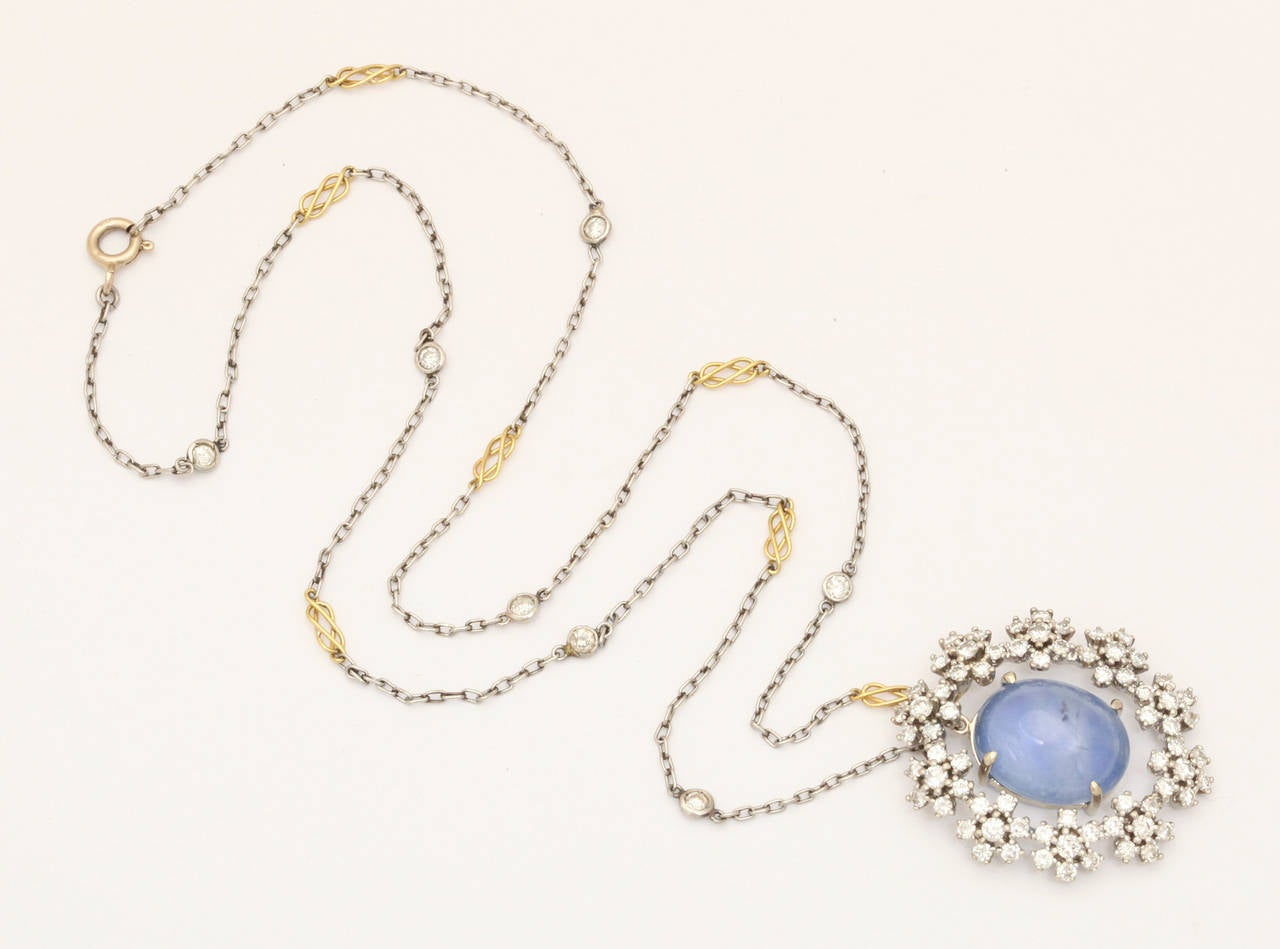 Diamond clusters of flowers form a halo of radiance around an opalescent star sapphire in this mid twentieth century pendant of 14kt white gold. The diamonds, deeply set, are modern cut and bright as they shine with a total approximate weight of
