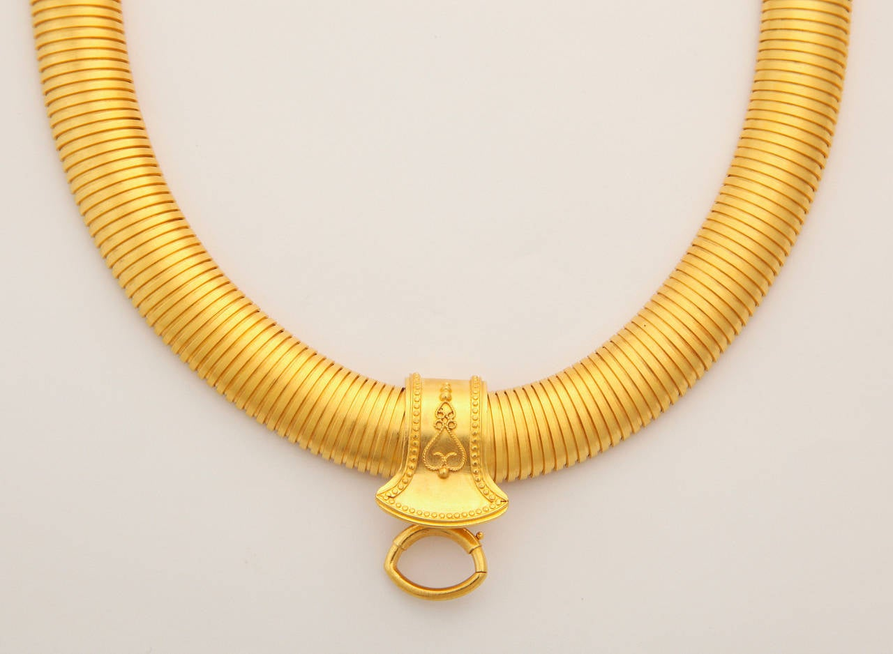 An ultra flexible, even stretchy, ultra wide Victorian snake chain collar in 18kt bloomed gold so gleaming that it is almost iridescent, is joined by a slide that slips off when desired. I first viewed this necklace without the slide and