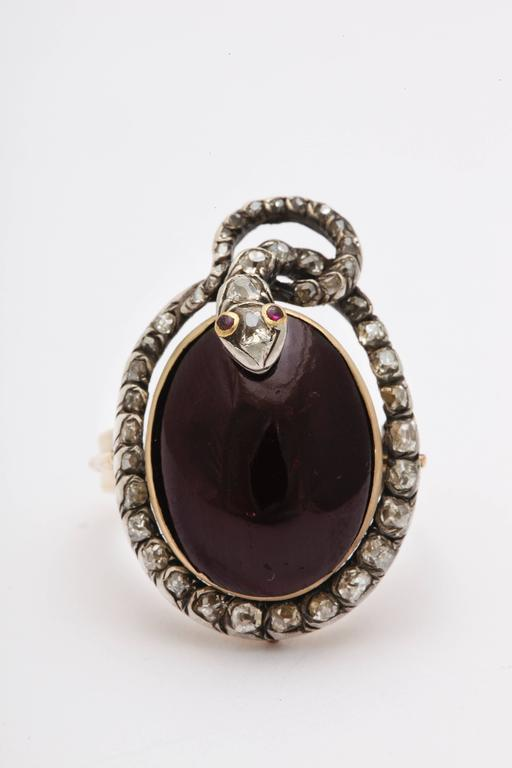 A coy diamond serpent coils around the large scale cabochon garnet of this ring like a love knot symbolizing endless loyalty and devotion. The diamonds of the serpent's body are off-round antique cut stones. The nose of the snake is set with a