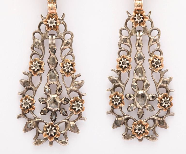 The diamonds are sparkling dewdrops throughout these lightweight, spiky, lacy Georgian earrings  set with antique diamonds and punctuated with gold flowers. The flowers hold small diamonds in their center. This is a pair of the most luscious
