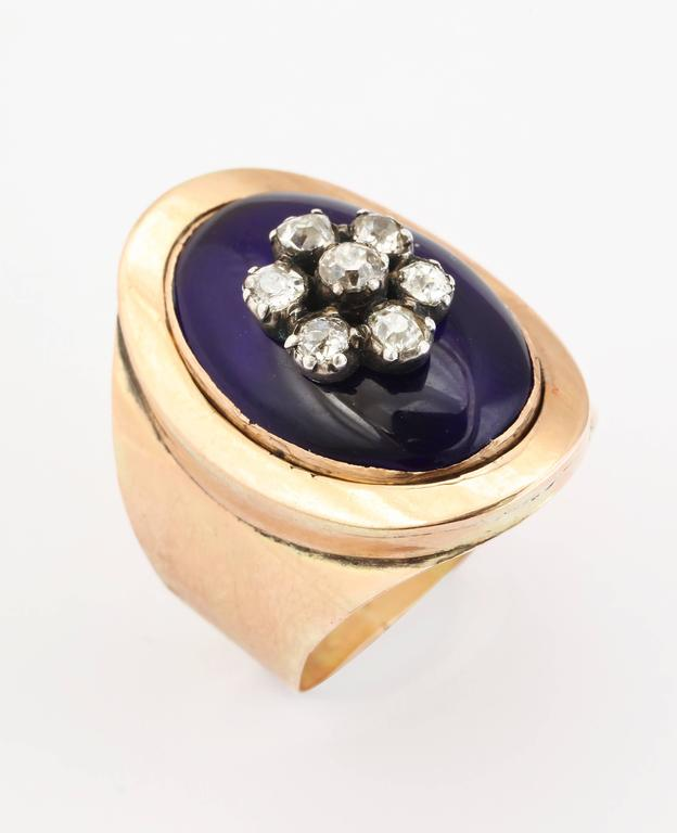 A stunning ring of 15 kt gold, lustrous medium blue enamel and a central diamond flower of antique diamonds makes an important appearance in its broad cigar band shank.  This is high on my list of favorite style antique rings. It curves to the