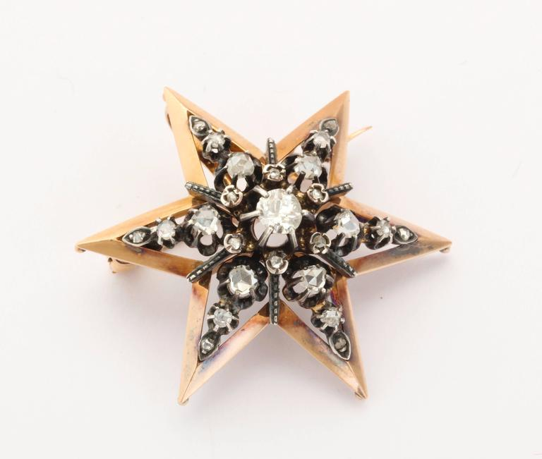 A star pendant or brooch boasts a central off round diamond sitting nestled in a cluster of rose cut stones. The diamonds sit forward in the 15 kt yellow gold frame, that has just a hint of rose tone, giving rich contrast to the white of the antique