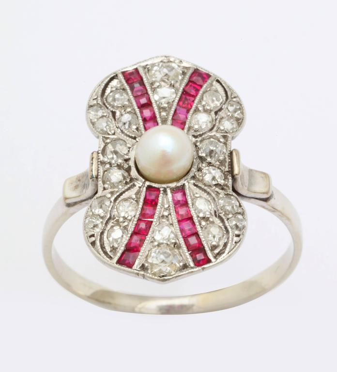 A ring that is a celebration of Art Deco color, form and geometry brings you converging rows of rubies on a background of diamonds, brought together with a central pearl. The outer form is an unusual, irregular bow that is gracefully pinched in the