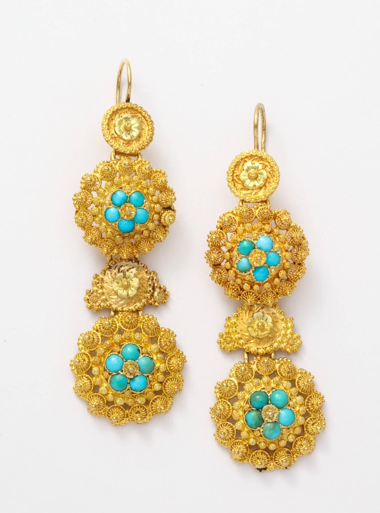 Fine cannetille work forms tight spirals in 18 kt gold that is punctuated with granulation and natural turquoise. There are four sections to these earrings and all are original to the 1840 construction. They are light on the ear. These are a