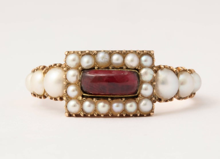 The gem quality is immediately visible in this treasure of a 15 kt gold natural pearl and garnet ring c. 1860. The pearls are lustrous and well matched as they frame the center garnet and spill graduated on the ring shoulders. Pearls were associated