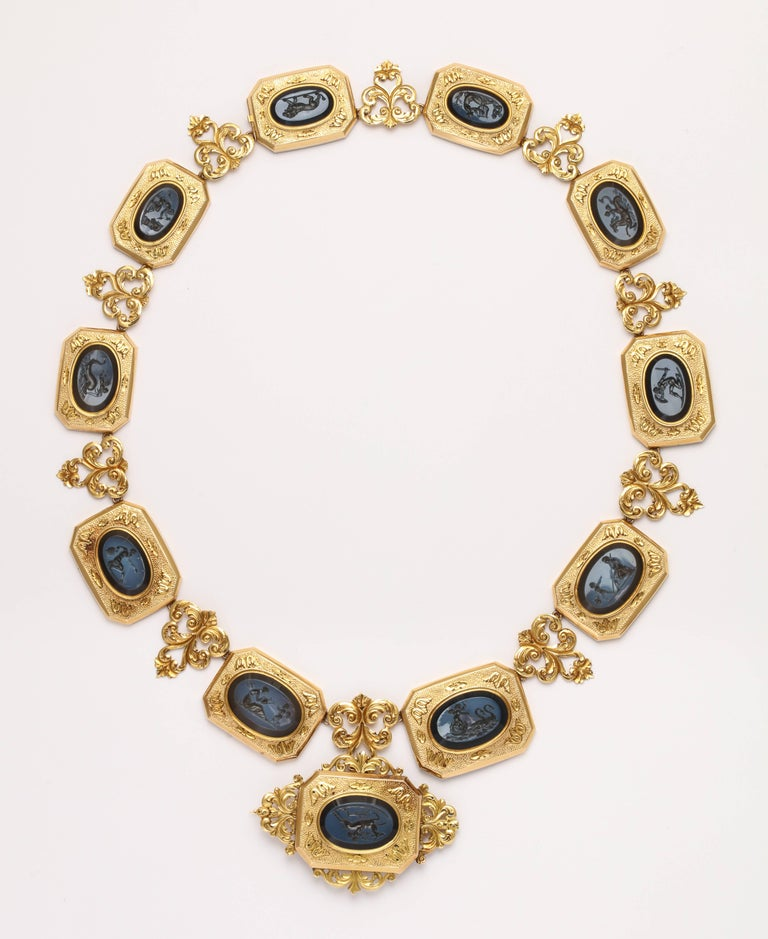 Eleven mythological scenes are carved in the raised grey-blue section of black banded agate and set in rectangular engraved and hammered plaques separated by architectural links of swirling acanthus leaves creating a necklace and brooch of splendor.