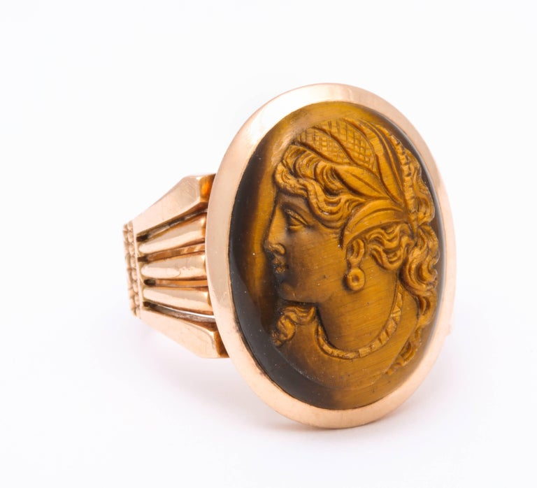 A substantial shank of 14 kt gold holds a gem tiger eye stone cameo of a sensuous classical woman, wearing a diadem engraved in crosshatch. The stone of two colors, carved to perfection in left profile, brings the golden woman forward flashing in