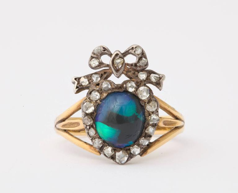 This beauty of a black opal and diamond ring touches the heart of the first to see it. The breath halts at the moment the color and iridescent glow strike the senses.  Its quality sings in celebration of a relationship to each who view it . The