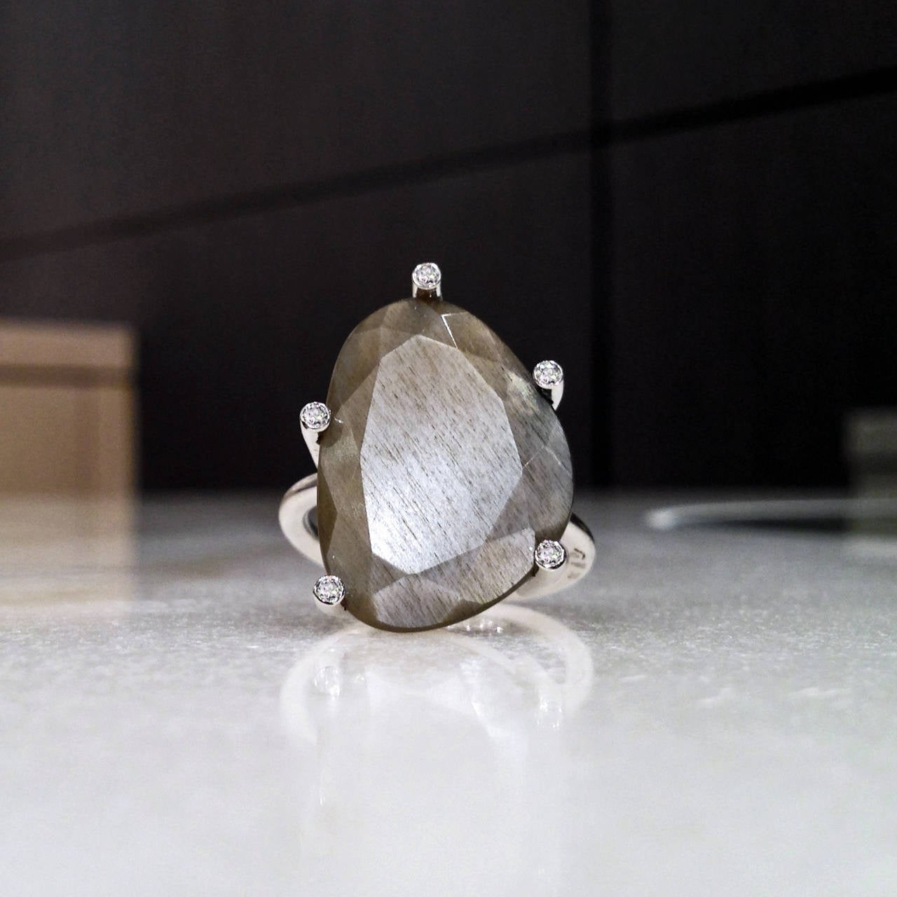 One-of-a-Kind Snowflake Ring handcrafted in 18k white gold showcasing a phenomenal 11.96 carat custom-cut-and-faceted gray moonstone, accented by 5 white, round brilliant-cut diamonds totaling 0.07 carats. Size 7.25 (Can be sized). 