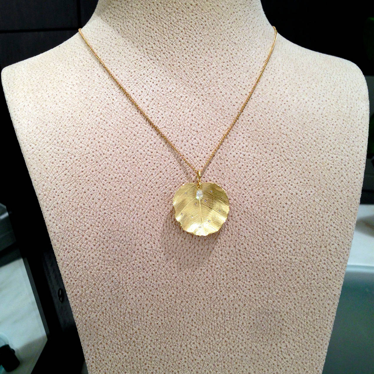 Lotus Leaf Necklace handcrafted by jewelry artist Barbara Heinrich in matte finished 18k yellow gold with a dangling 0.28 carat white diamond briolette drop and accompanied by 0.05 total carats of bezel-set round brilliant-cut white diamonds.