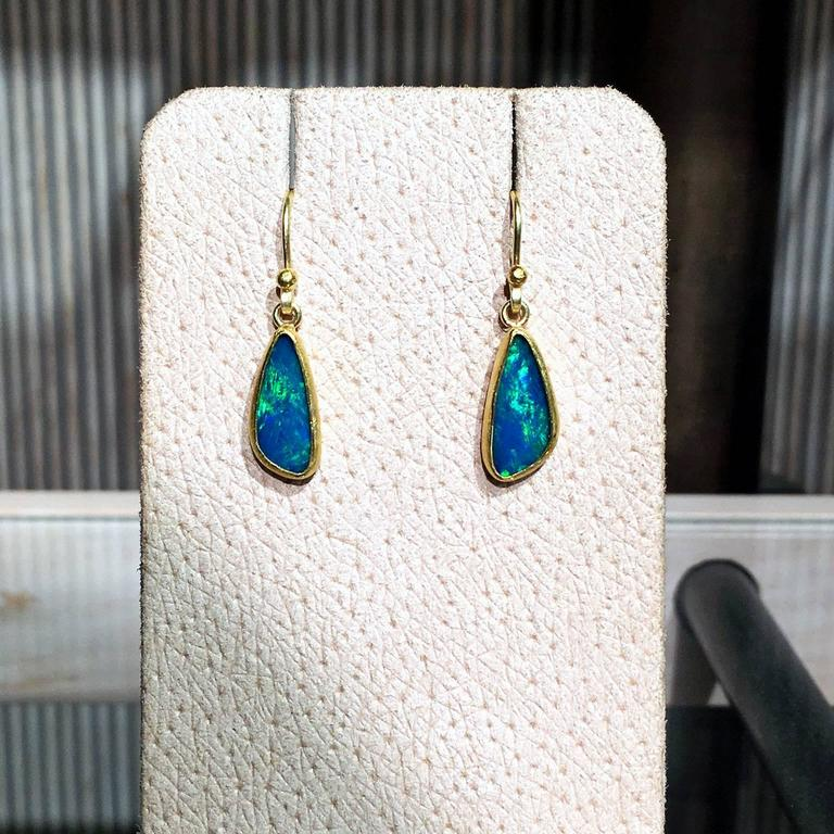 Dangling Drop Earrings handcrafted by Petra Class in her signature 22k yellow gold finish with two bezel-set Australian blue opal doublets showcasing a beautiful green flash and on 18k yellow gold wires.  Stamped and Hallmarked 18k / 22k / PC