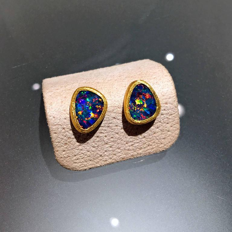 One-of-a-Kind Stud Earrings handcrafted by acclaimed jewelry designer Devta Doolan with bluish violet opal doublets exhibiting a unique and vibrant rare red flash with electrifying accents of green, orange, blue, yellow, violet, and purple fire. The