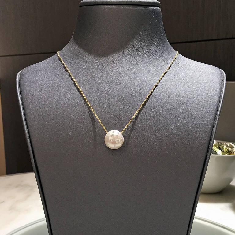 Freshwater Pearl Drop Necklace by renowned jewelry designer showcases a stunning, lustrous white freshwater pearl (12mm x 12mm x 10mm) with pink and violet tone. The pearl features 0.38 total carats of Russell's signature embedded round