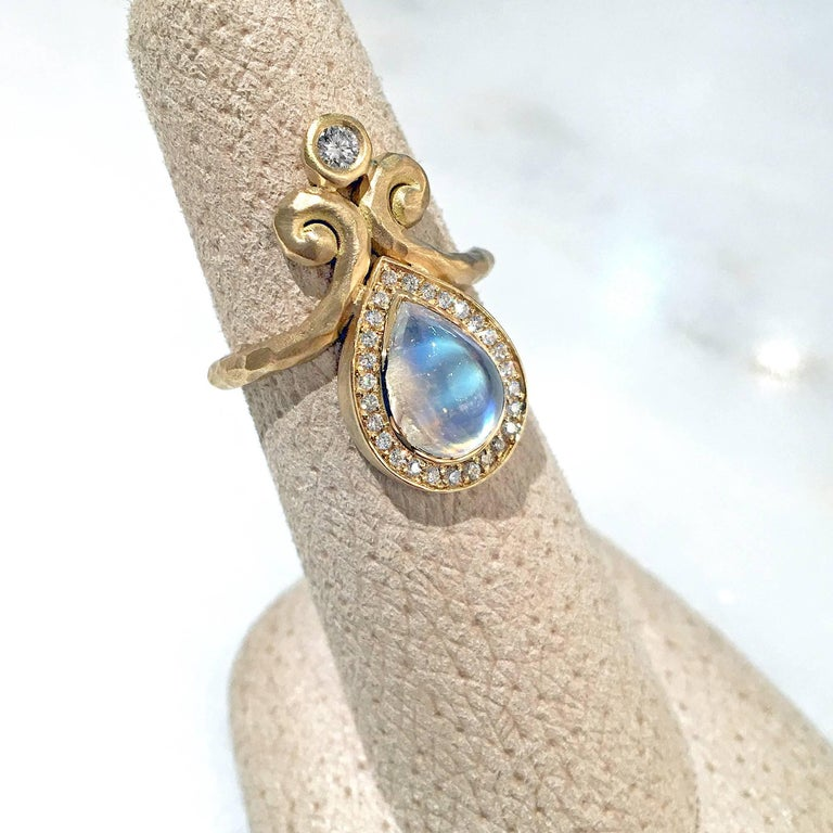 One of a Kind Ring handcrafted by jewelry designer Pamela Froman in hand-hammered 18k yellow gold featuring a spectacular 2.79 carat pear-shaped rainbow moonstone cabochon surrounded by a pave' diamond bezel and accented with a substantial round