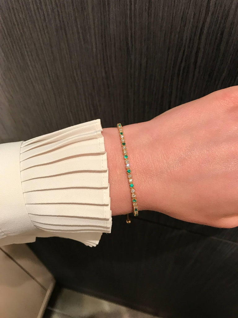 One of a Kind Bolo Bracelet handmade in 18k yellow gold by jewelry designer Fern Freeman featuring 0.45 carats of round brilliant-cut emerald and round brilliant-cut white diamonds totaling 0.96 carats. The solid 18k gold faceted bolo element slides