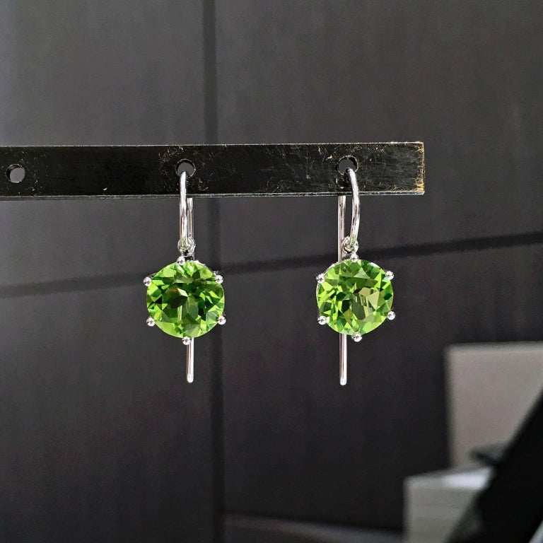 Princess Earrings, handcrafted by acclaimed jewelry artist and master metalsmith Erich Zimmermann, in 18k white gold with a gorgeous,  fiery matched pair of 9mm slightly yellowish green peridot totaling 6.80 carats set with six ball prongs in an