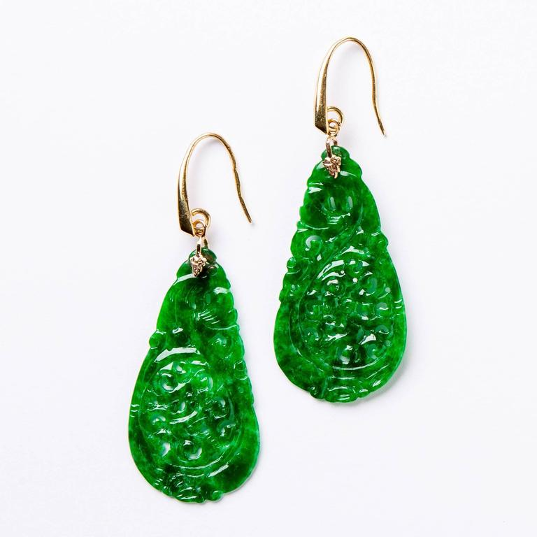 Delicate lightweight carved green jade pear shaped drop earrings with 18 karat gold.