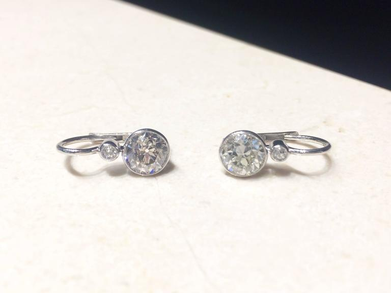 One pair of pre-owned 14kt white gold drop old cut diamond earrings. Approximately 2.20 total carat weight. Graded at SI1-SI2 / H-I. Four round diamonds bezel set.  Weight approximately 2.5 grams, measuring approximately 3/4 inch.