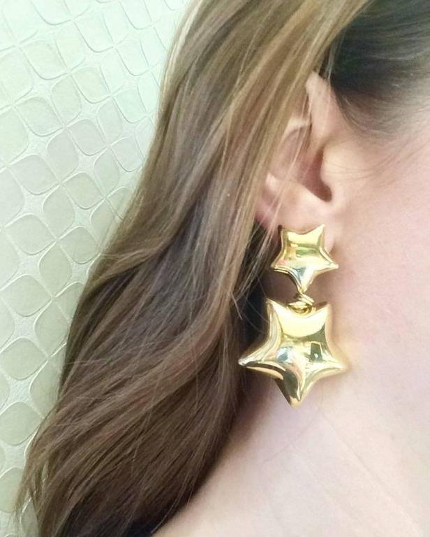 These 18kt yellow gold double star drop earrings that are sure to impress.  What a fun statement pair of earrings to wear and enjoy.  Made for pierced ears with an omega European style clip to hold them securely in place. They weigh approximately 22