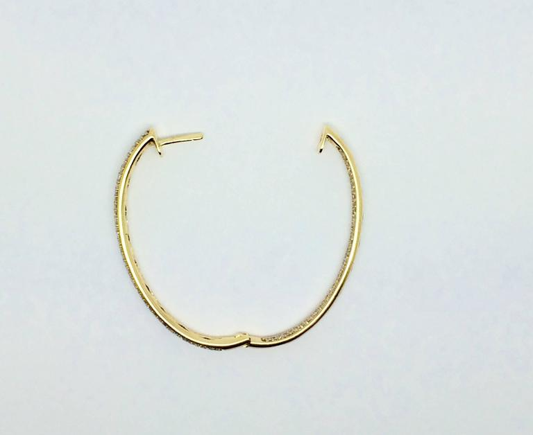 Hoop style earrings in 18k yellow gold with pave set round brilliant cut diamonds. Carat total weight approximately 2.24.