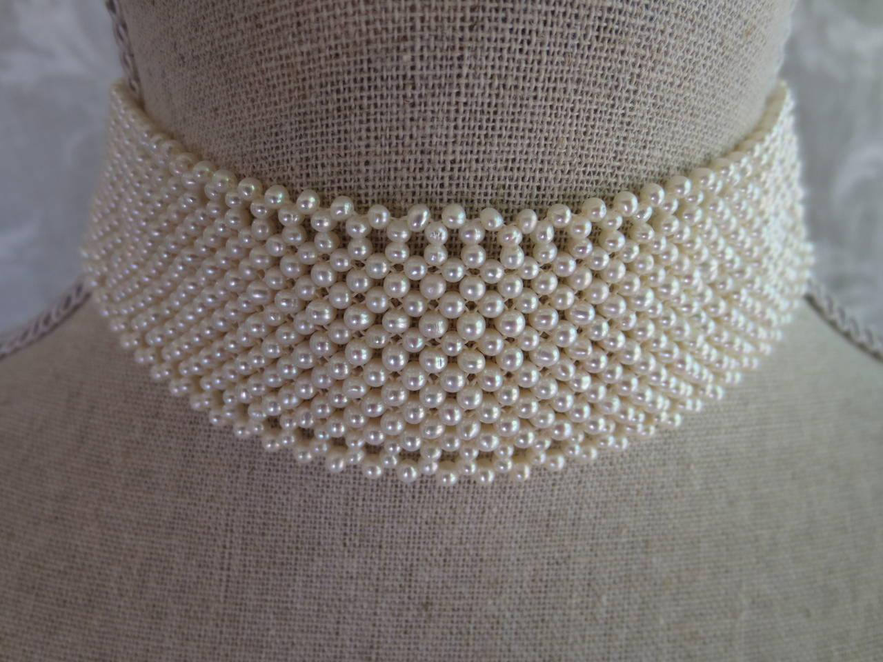 "2 - 2.5 mm cultured pearls are intricately hand woven to create a delicate lacelike design. Choker measures 13"" in length and 1.25"" in height. Choker is tapered in design to fit along the curve of the neckline. The choker is so beautifully tapered"